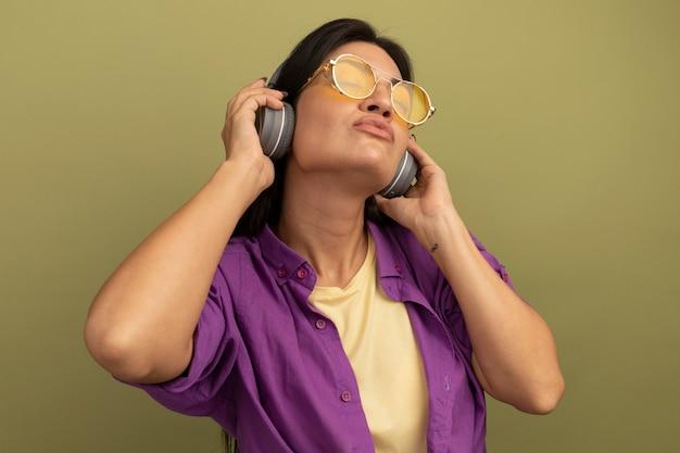 Tranquilla bella donna castana in occhiali da sole con le cuffie sta con gli occhi chiusi isolati sulla parete verde oliva