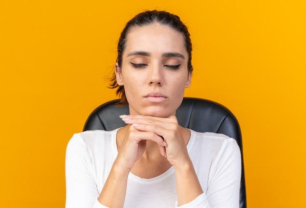 화장 도구가 있는 테이블에 눈을 감고 앉아 있는 평화로운 백인 여성은 복사 공간이 있는 주황색 벽에 격리된 손에 턱을 대고 있습니다.