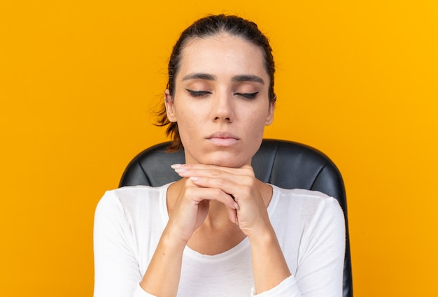 Donna abbastanza caucasica pacifica seduta con gli occhi chiusi al tavolo con strumenti per il trucco che si mette il mento sulle mani isolato sul muro arancione con spazio di copia