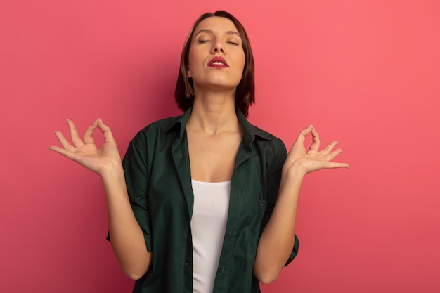 Peaceful pretty woman stands with closed eyes pretending to meditate isolated on pink wall