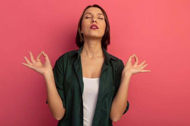 Мирная красивая женщина стоит с закрытыми глазами, делая вид, что медитирует, изолирована на розовой стене