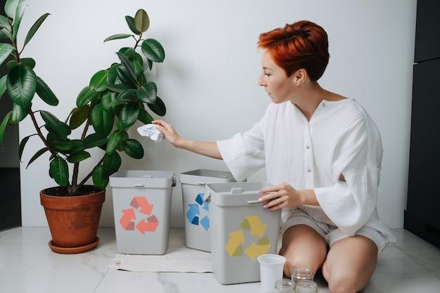 Мирная рыжеволосая женщина сидит на ногах, сортируя мусор между небольшими мусорными баками у себя дома. на них нанесены стрелки разного цвета. держа лист бумаги.