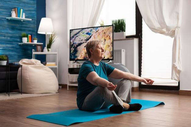 Мирная пенсионерка медитирует во время медитационной ретритной тренировки, удобно сидя в позе лотоса с закрытыми глазами на коврике для йоги