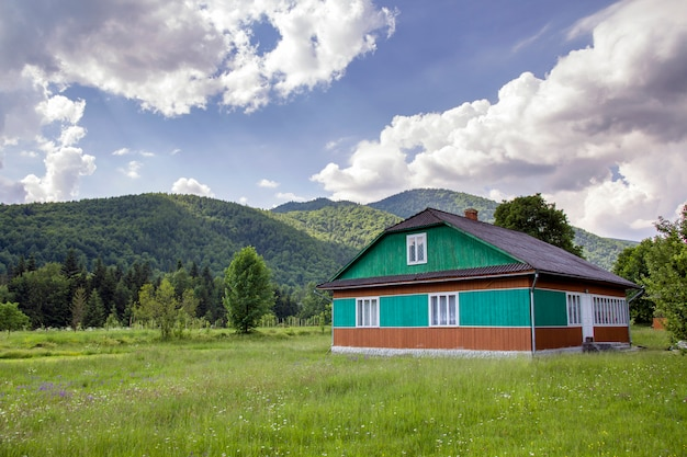 Peaceful rural summer landscape on bright sunny day. lit by sun beautiful wooden residential house painted in green, blue and brown colors on grassy blooming meadow on forested mountains.