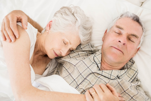 Peaceful senior couple sleeping on bed