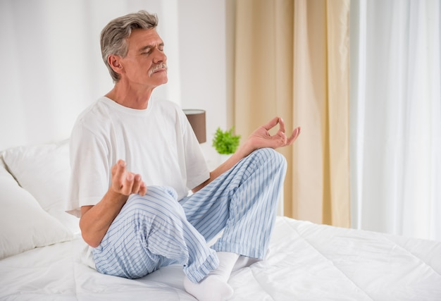 Peaceful senior man meditating seated on a bed.