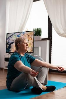Мирная старшая женщина, удобно сидящая в позе лотоса на коврике для йоги с закрытыми глазами, практикующими медитацию. спокойный пенсионер упражнения фитнес-тело во время тренировки медитации в гостиной