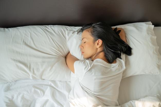 静かで穏やかな若い女性は、ベッドで眠っているパジャマを着ています。上面図