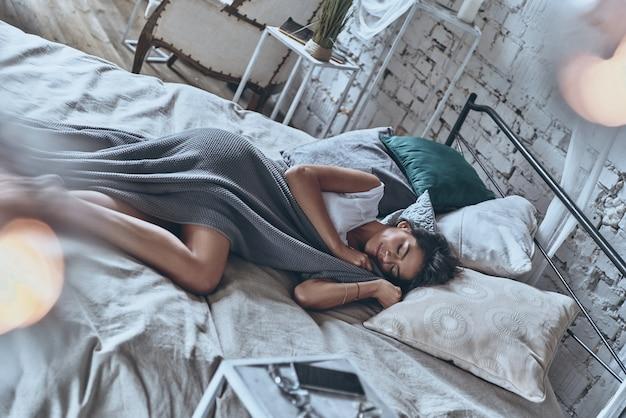 Спокойный сон. вид сверху привлекательной молодой женщины, покрытой одеялом, с закрытыми глазами