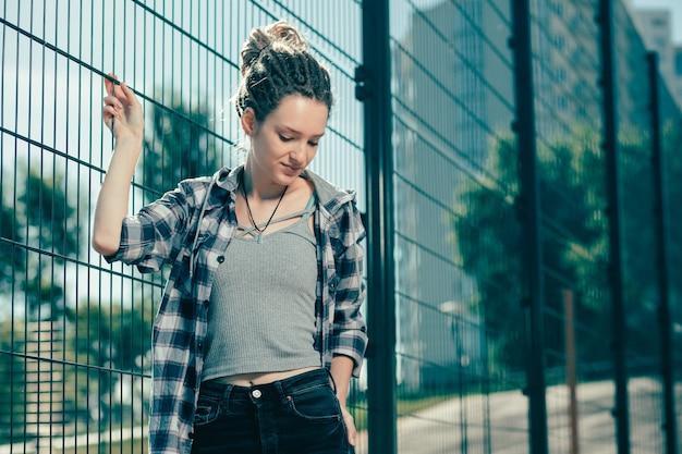 カジュアルな服を着て、金網柵の近くに立っている間少し微笑んでいる平和な思いやりのある女性