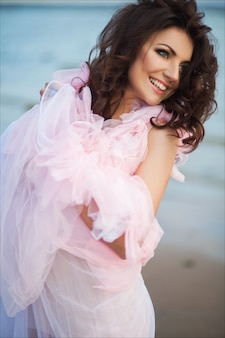 Peaceful vacation paradise woman walking on sunset ocean beach. smiling excited girl in pink romantic dress