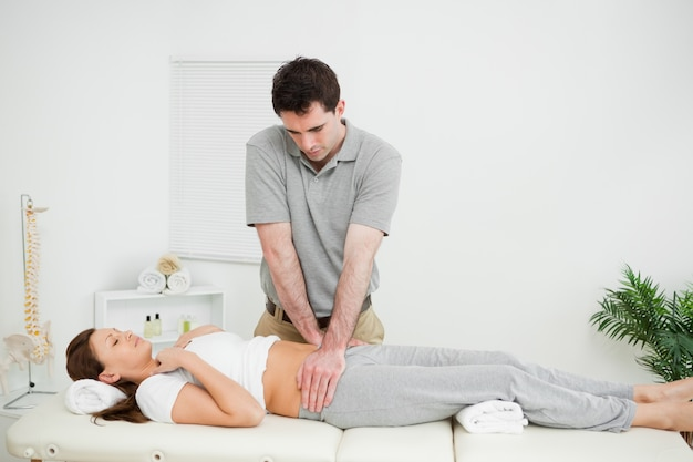 Peaceful woman being touched by an osteopath