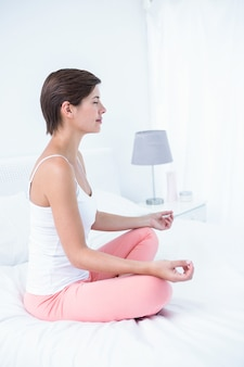 Peaceful woman doing yoga in her bed