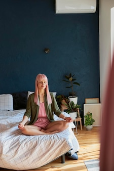 ゆったりとしたシャツとパジャマを着た平和な女性がbadroomで瞑想します