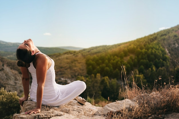 Peaceful woman meditating in countryside