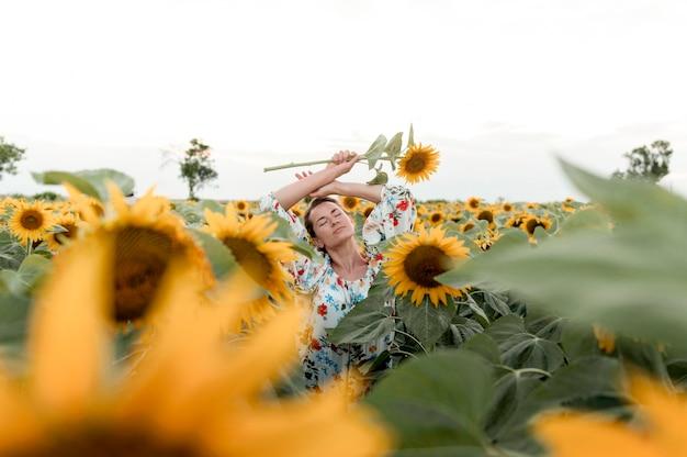 ひまわり畑でポーズをとって穏やかな女性