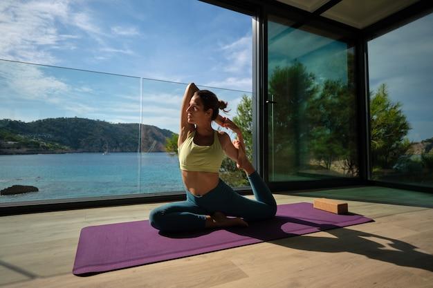 Peaceful woman practicing yoga in mermaid asana