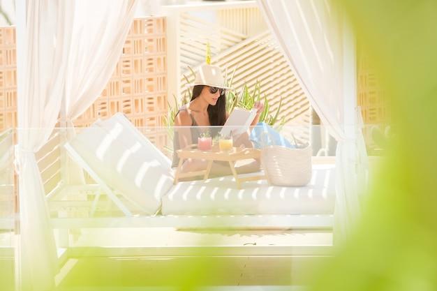 Мирная женщина, читающая книгу на кровати с балдахином на террасе
