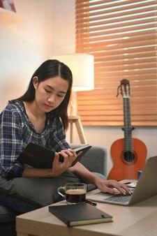 Мирная женщина, читающая книгу на софе у себя дома.