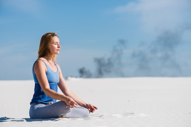 Peaceful woman sits in lotus yoga pose
