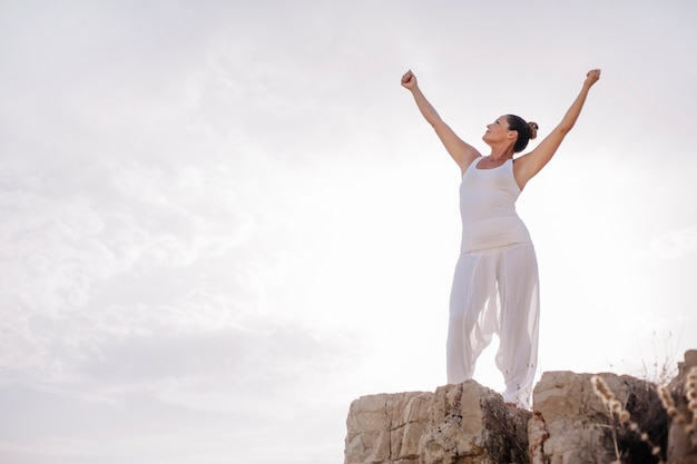Peaceful woman stretching arms on rock