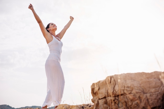 Peaceful woman stretching arms towards sky