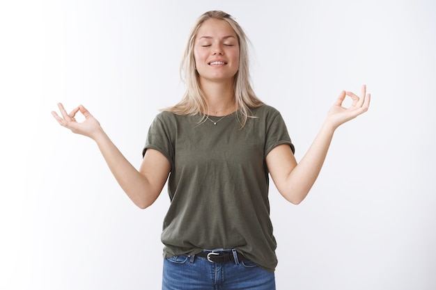 Peaceful young attractive 25s woman with blond hair inhaling fresh air close eyes and smiling relieved and happy meditating in lotus pose with mudra signs sideways against white background