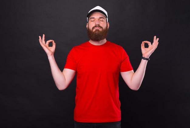 검정을 통해 선 제스처를 만드는 빨간 티셔츠에 평화로운 젊은 수염 난된 남자