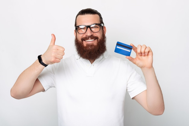Peaceful young bearded man recommends this card he is showing.