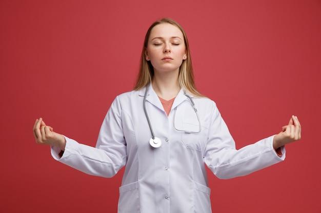 目を閉じて瞑想する首の周りに医療ローブと聴診器を身に着けている平和な若いブロンドの女性医師