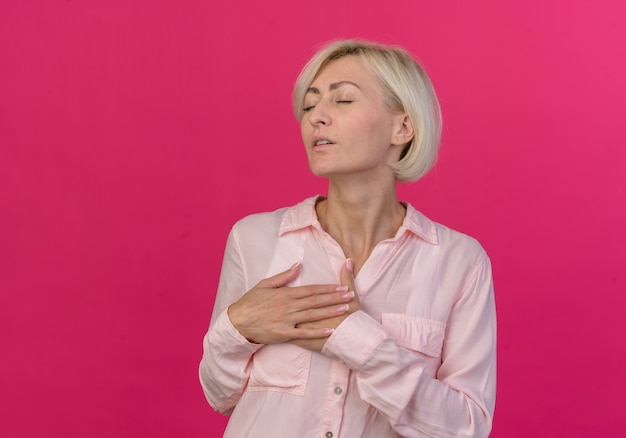 Tranquilla giovane bionda donna slava mantenendo le mani sul petto con gli occhi chiusi isolati su sfondo rosa con copia spazio