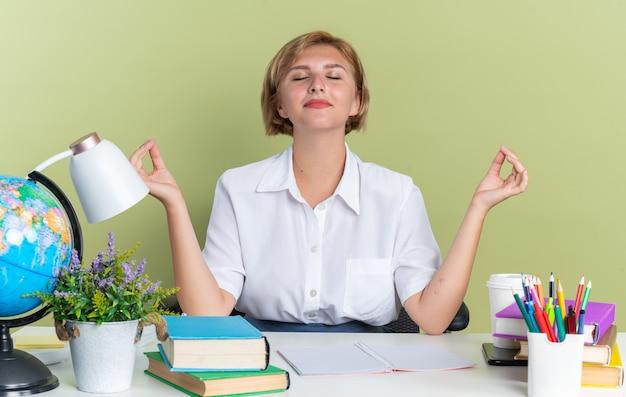 Una giovane studentessa bionda pacifica seduta alla scrivania con gli strumenti della scuola che medita con gli occhi chiusi isolati su un muro verde oliva