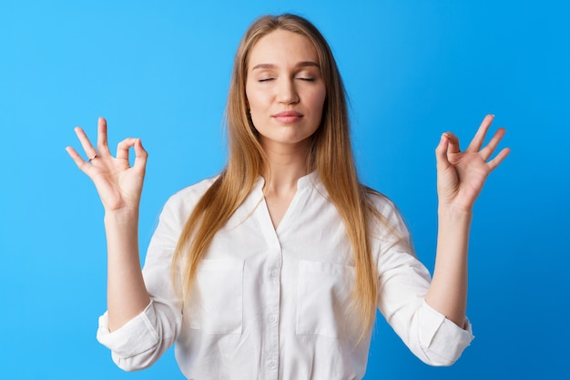 Peaceful young blonde woman portrait in zen pose against blue background