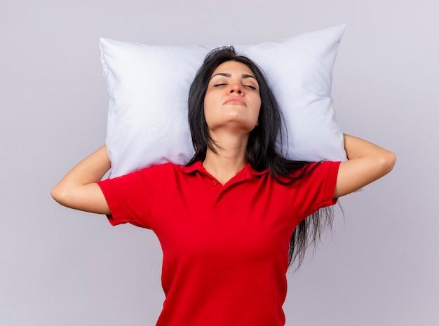 Мирная молодая кавказская больная девочка, держащая подушку под головой, притворяется, спит с закрытыми глазами, изолированными на белом фоне
