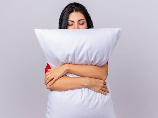 Tranquilla giovane ragazza malata caucasica abbracciando cuscino con gli occhi chiusi isolati su sfondo bianco con spazio di copia