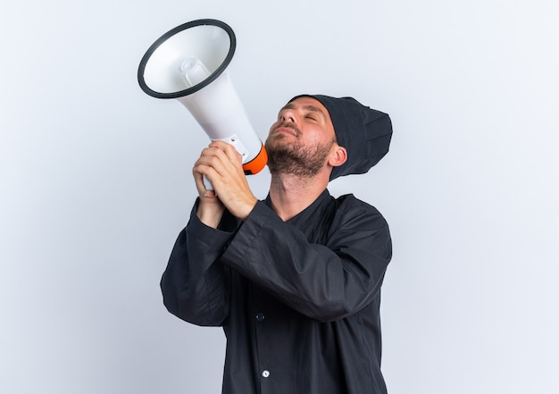 Tranquillo giovane maschio caucasico cuoco in uniforme da chef e berretto che tiene l'altoparlante inclinando la testa all'indietro con gli occhi chiusi isolato sul muro bianco con spazio di copia
