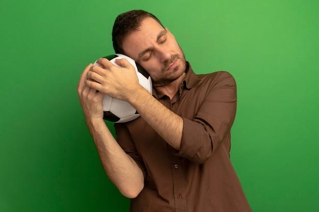 Tranquillo giovane uomo caucasico tenendo il pallone da calcio mettendo la testa su di esso con gli occhi chiusi isolati su sfondo verde con copia spazio