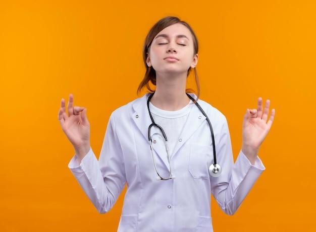 Мирная молодая женщина-врач в медицинском халате и стетоскопе делает знак ок с закрытыми глазами на изолированном оранжевом пространстве