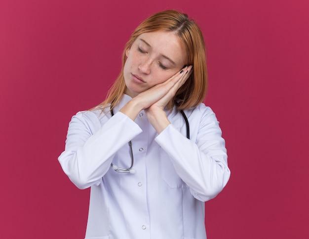 평화로운 젊은 여성 생강 의사는 의료 가운과 청진기를 입고 수면 제스처를 취합니다.