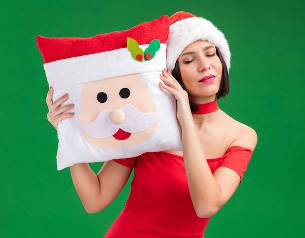 Мирная молодая девушка в шляпе санта-клауса держит подушку санта-клауса, касаясь ею головы с закрытыми глазами, изолированными на зеленой стене