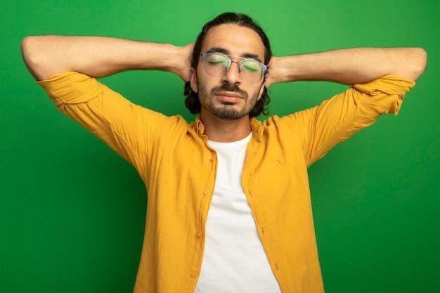 Мирный молодой красивый кавказский мужчина в очках, держа руки за головой с закрытыми глазами, изолированными на зеленом фоне