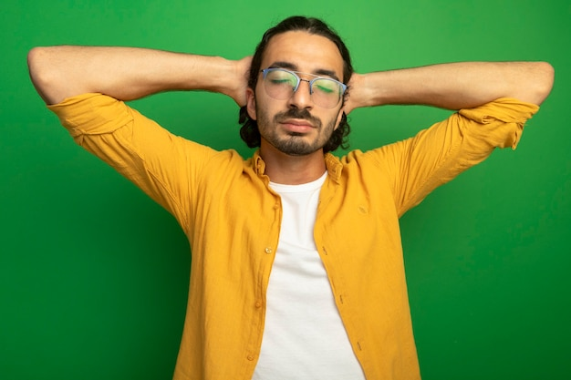 Tranquillo giovane uomo caucasico bello con gli occhiali mantenendo le mani dietro la testa con gli occhi chiusi isolati su sfondo verde