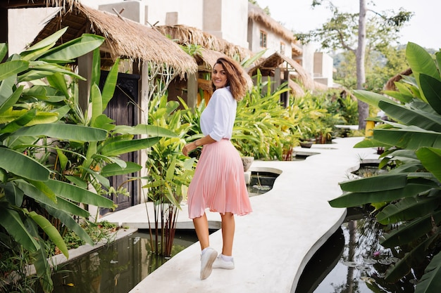 Peaceful young happy woman with short curly hair in pink long skirt and white shirt alone outside her villa