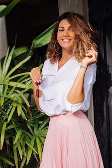 Tranquilla giovane donna felice con i capelli ricci corti in gonna lunga rosa e camicia bianca da solo fuori dalla sua villa