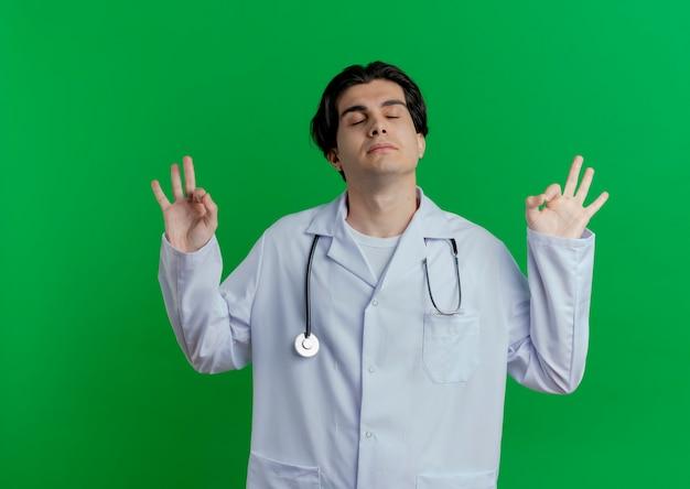 Tranquillo giovane medico maschio che indossa abito medico e stetoscopio facendo segni ok con gli occhi chiusi isolati sulla parete verde con lo spazio della copia