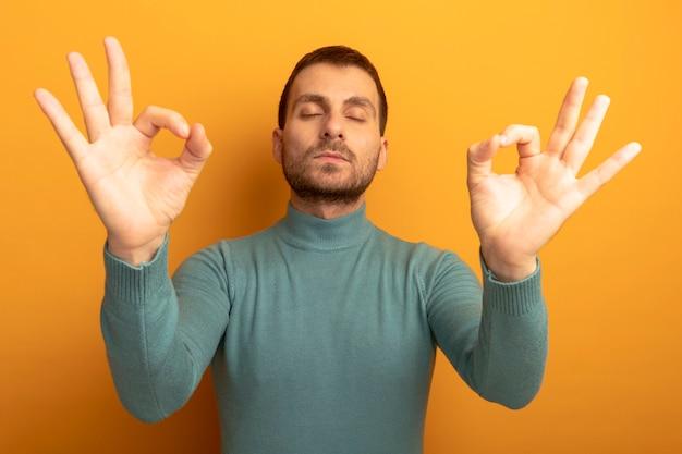 주황색 벽에 고립 된 닫힌 눈으로 확인 표시를하고 평화로운 젊은 남자