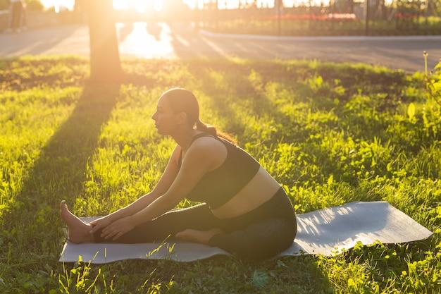 体操服を着た平和な若いポジティブな妊婦は、晴れた暖かい夏の日にヨガをし、緑の芝生のマットの上に座って瞑想します。出産の準備と前向きな姿勢の概念