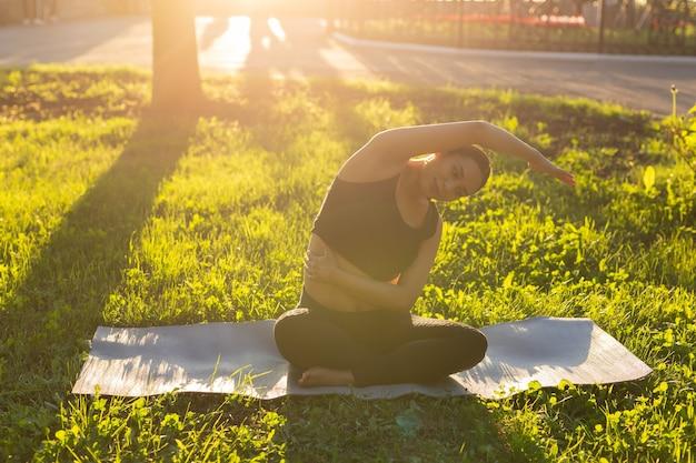 Мирная молодая позитивная беременная женщина в гимнастическом костюме занимается йогой и медитирует, сидя на циновке на зеленой траве в солнечный теплый летний день. концепция подготовки к родам и позитивный настрой