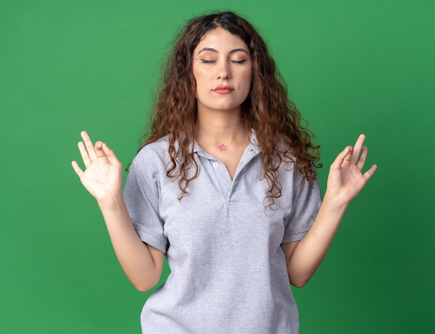 Peaceful young pretty caucasian girl meditating with closed eyes isolated on green wall