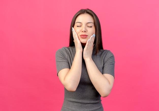 Tranquilla giovane donna graziosa che mette le mani sul viso con gli occhi chiusi isolati su sfondo rosa con copia spazio